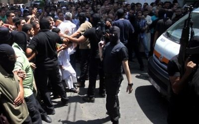 Un Palestinien armé et masqué repousse une foule de croyants devant la mosquée de Gaza Ville après la prière du vendredi, avant l'exécution de 18 hommes qui auraient collaboré avec Israël, le 22 août 2O14. (Crédit : AFP)