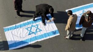 Des manifestants iraniens versent du kérosène sur un drapeau israélien pendant les funérailles du brigadier-général Mohammad Ali Allahdi à Téhéran, le 21 janvier 2015. Allahdi, un commandant des Gardiens de la Révolution en Iran, a été tué dans une frappe aérienne en Syrie attribuée à Israël. (AFP / Atta Kenare)