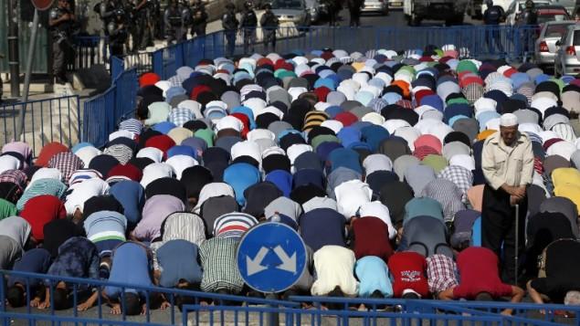 les forces de sécurité israéliennes montent la garde pendant que les fidèles musulmans palestiniens prennent part à la prière du vendredi à midi dans le quartier de Ras al-Amud à Jérusalem-Est, le 16 octobre, 2015 (Crédit : AFP / AHMAD GHARABLI)