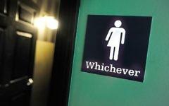 Signe des toilettes mixtes à Oval Park Grill, à Durham, Caroline du Nord, le 11 mai 2016. (Crédit : Sara D. Davis/Getty Images/AFP)