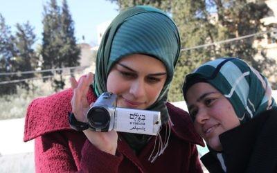 Une volontaire palestinienne de l'organisation des droits de l'homme B'Tselem apprend comment utiliser une caméra vidéo pour documenter les actions de Tsahal et des résidents des implantations de Cisjordanie, en 2014 (Crédit : B'Tselem/CC BY 4.0)