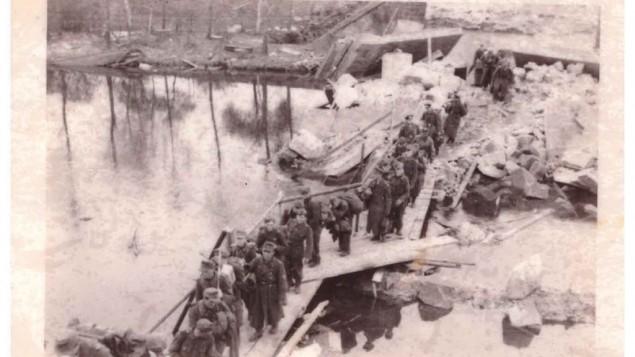 """""""Prisonniers de guerre allemands traversant la rivière Mulde sur un pont improvisé. Ces nazis ont choisi de se rendre à la 104e plutôt qu'aux Russes"""". Avril 1945, près de Bitterfeld, en Allemagne. (Crédit : Jules Helfner)"""