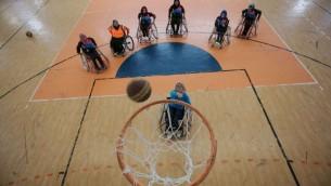 Une femme palestinienne marque un panier lors d'un entraînement de basket paralympique dirigé par l'Américain Jess Markt, le 28 mai 2016. (Crédits : Said Khatib / AFP)