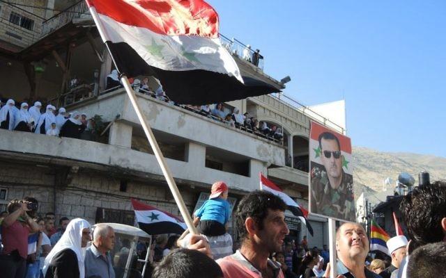 Un homme porte un drapeau syrien et un poster du présidet Bashar Al Assad au cours d'une manifestation pro armée syrienne, à Majdal Shams, lundi (Crédit : Melanie Lidman/Times of Israel)