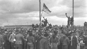 Dachau, Allemagne. Des prisonniers du camp de concentration brandissent le drapeau américain après leur libération (Crédits : archives de Yad Vashem)