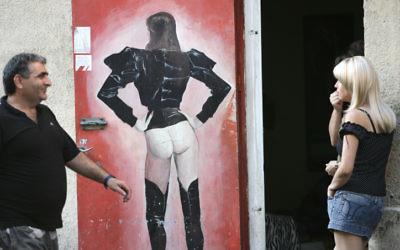 Un homme souriant à une jeune femme devant une maison close de Tel Aviv, le 21 septembre 2008. (Crédit : Kobi Gideon/Flash90)