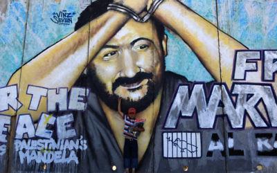 Un enfant palestinien devant un graffiti représentant Marwan Barghouthi, dirigeant palestinien emprisonné en Israël pour le meurtre de cinq Israéliens, au checkpoint de Qalandia, entre Ramallah et Jérusalem, en juin 2009. (Crédit : Kobi Gideon/Flash90)