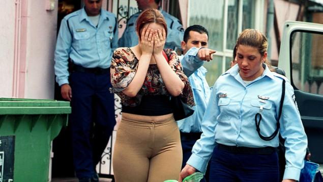 La police de l'immigration pendant la déportation de prostituées d'Europe de l'Est près de Haïfa. (Crédit : Moshe Shai/Flash90)