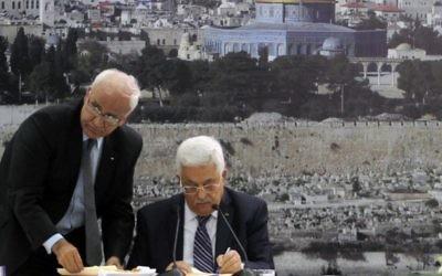 Le président de l'Autorité palestinienne, Mahmoud Abbas (à droite) et le responsable des négociations pour la paix, Saeb Erekat, signent une candidature pour intégrer les organismes de l'ONU, à Ramallah, en Cisjordanie, le mardi 1er avril 2014. (Crédit : Issam Rimawi/Flash90)