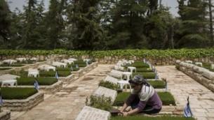 Une Israélienne allume une bougie sur une tombe au cimetière militaire national du mont Herzl, à Jérusalem, le 20 avril 2015. (Crédit : Yonatan Sindel/Flash90)