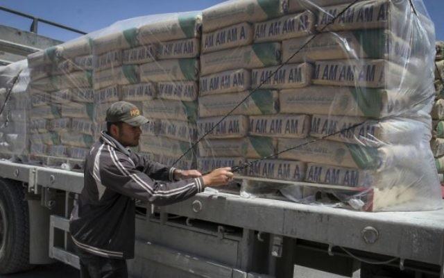Un Palestinien ajuste les sacs de ciment chargés sur un camion après leur entrée dans le sud de la bande de Gaza depuis Israël, via le poste-frontière Keren Shalom à Rafah, le 29 avril 2015. (Crédit : Abed Rahim Khatib /Flash 90)