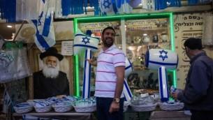 Un homme devant un magasin vendant des objets frappés du drapeau israélien avant le 68e Jour de l'Indépendance d'Israël, à Ashkelon, dans le sud du pays, le 8 mai 2016. (Crédit : Corinna Kern/Flash90)