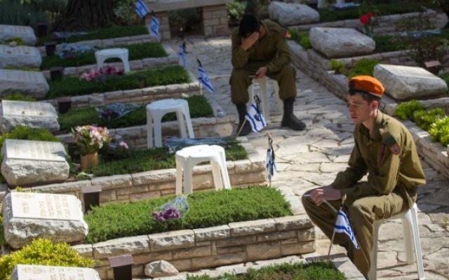 Soldats israéliens en deuil sur les tombes des soldats tombés au cimetière militaire du mont Herzl, à Jérusalem, le Jour du Souvenir, le 11 mai 2016. (Crédit : Miriam Alster/Flash90)