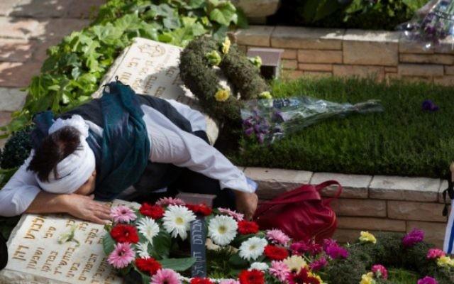 Des Israéliens en deuil sur les tombes des soldats tombés au cimetière militaire du mont Herzl, à Jérusalem, le Jour du Souvenir, le 11 mai 2016. (Crédit : Miriam Alster/Flash90)