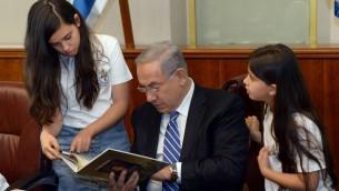 Des enfants de l'Organisation des Veuves et des Orphelins de Tsahal, avec le Premier ministre Benjamin Netanyahu avant le Jour du Souvenir d'Israël,d ans le bureau du Premier ministre, le 9 mai 2016. (Crédit : Haim Tzach/GPO)