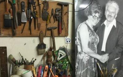 La table à dessin et les outils de Joseph Bau sont toujours en place dans son studio, sous un portrait de lui avec sa femme, Rebecca Tennebaum. (Crédit : Jessica Steinberg/Times of Israel)
