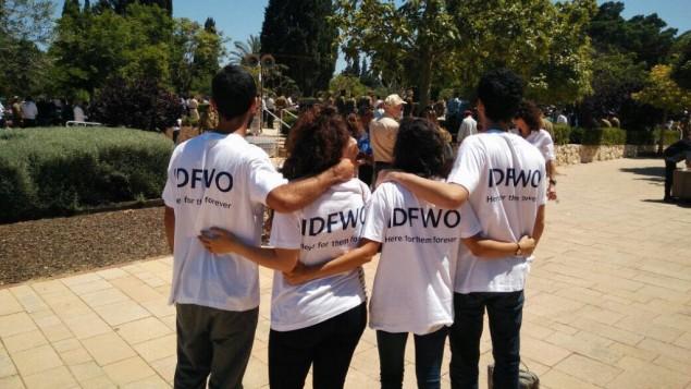 Membres de l'Organisation des veuves et orphelins de Tsahal en visite aux familles endeuillées sur les tombes de leurs proches au cimetière du mont Herzl, à Jérusalem, le 11 mai 2016. (Crédit : autorisation)