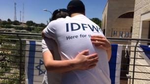 Shlomi Nachumson, jeune directeur de l'Organisation des veuves et orphelins de Tsahal, prend dans ses bras un enfant orphelin dans sa maison de Cisjordanie, le 11 mai 2016. (Crédit : autorisation)
