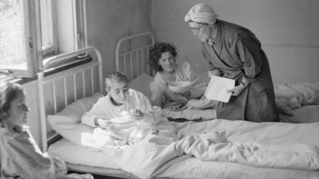 Un travailleur social britannique s'occupe des survivants du camp de concentration de Bergen-Belsen peu de temps après sa libération (Crédit : Imperial War Museum)