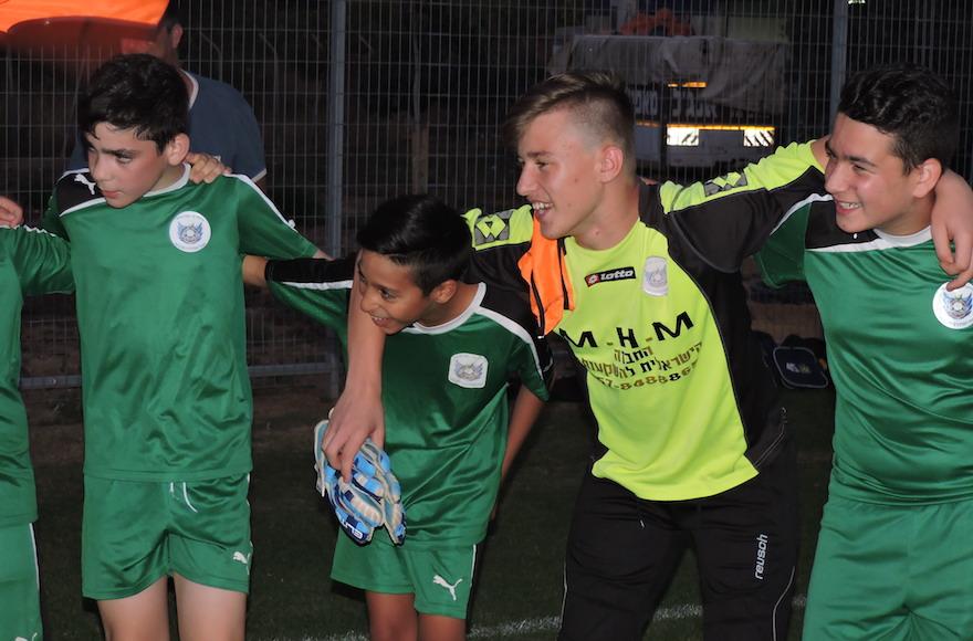 Les membres de l'équipe de football des 13 ans de Tzav Pius 13 dans la ville de Pardes Hanna chantant l'hymne de l'équipe suite à un entrainement (Crédit : Ben Sales)