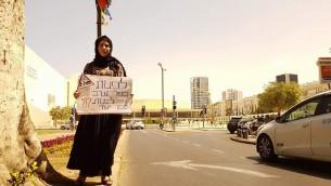 """Une femme bédouin pendant une manifestation pour le village d'Umm al-Hiran sur une rue centrale de Tel Aviv, avec un panneau """"Evacuer un village arabe pour en construire un juif ?"""", le 20 mai 2016. (Crédit : porte-parole de la Liste arabe unie)"""