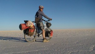 Sadan traversant les marais salants sur Emuna, son vélo hybride Thorn bleu et blanc, lors de son voyage autour du monde de 2007 à 2011 (Crédit : autorisation Roei Sadan).