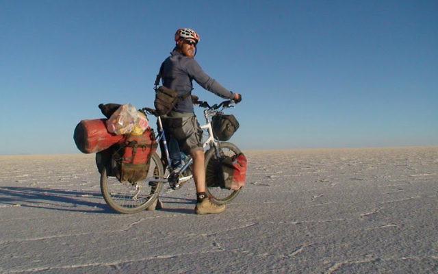 Sadan traversant les marais salants sur Emuna, son vélo hybride Thorn bleu et blanc, lors de son voyage autour du monde de 2007 à 2011. (Crédit : Autorisation Roei Sadan)