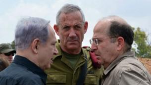 Le Premier ministre Benjamin Netanyahu (à gauche) avec le chef d'Etat-major d'alors, Benny Gantz (au centre) et le ministre de la Défense de l'époque Moshe Yaalon (à droite) dans le sud d'Israël, pendant la guerre contre le Hamas, le 21 juillet 2014. (Crédit : Kobi Gideon/GPO/Flash90)