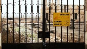 """Une porte scellée empêche les visiteurs d'approcher d'une église à Qasr el-Yehud, le site du Jourdain où Jésus aurait été baptisé. Le panneau sur la porte dit """"Danger ! Mines !"""" en hébreu, arabe et anglais. (Crédit : capture d'écran YouTube)"""