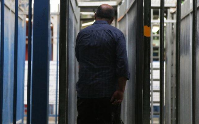 """Un travailleur palestinien entrant dans la """"manche"""" en métal avant que son identité ne soit vérifiée au checkpoint de Qalandiya, le 3 mai 2016. (Crédit : Luke Tress/Times of Israel)."""