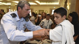 Le grand rabbin de l'armée israélienne, Rafi Peretz, apprend à un orphelin à mettre ses tefilins pour la première fois pendant une cérémonie de bar mitzvah organisée par l'Organisation des veuves et des orphelins de Tsahal, photographie non datée. (Crédit : autorisation)