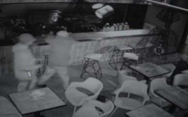 Deux hommes aspergent un restaurant casher d'un liquide avant qu'il ne brûle, à Manchester, en Angleterre, le 6 mai 2016. (Crédit : capture d'écran des vidéos de caméras de sécurité)