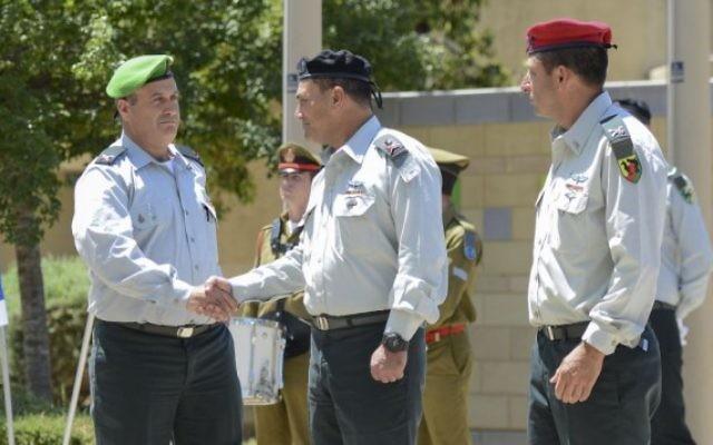 Le nouveau chef de la Division de Gaza, le Brigadier général Yehuda Fuchs, à gauche, serre la main au chef du Commandement Sud, le général Eyal Zamir au cours de la cérémonie de sortie du Brigadier général Itay Virov, à droite, à la base de la Division, près de la frontière de Gaza, le 19 mai 2016 (Crédit unité du porte-parole de Tsahal)