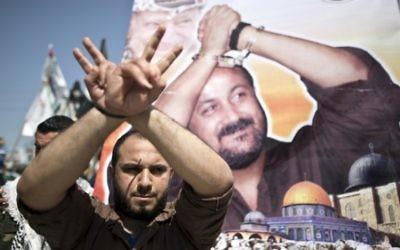 Un Palestinien prend la pose devant une affiche du leader du Fatah actuellement en prison, Marwan Barghouthi, au cours d'une manifestation pour le Jour des Palestiniens emprisonnés, à Gaza Ville, le 17 avril 2016. (Crédit : Mahmud Hams/AFP)
