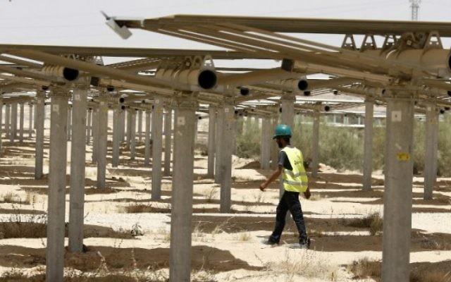 Un ouvrier passe sous les 55 000 miroirs redirigeant la lumière vers la tour solaire Ashalim, dans le désert du Néguev, le 26 mai 2016. (Crédit : Jack Guez/AFP)
