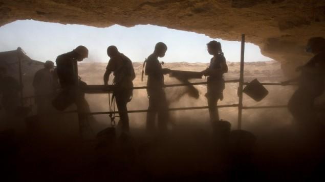 Bénévoles israéliens et étrangers prennent part aux fouilles d'une grotte du Canyon Tzeelim, au-dessus de la mer Morte, dans le désert de Judée, le 1er juin 2016. (Crédit : AFP/Menahem Kahana)