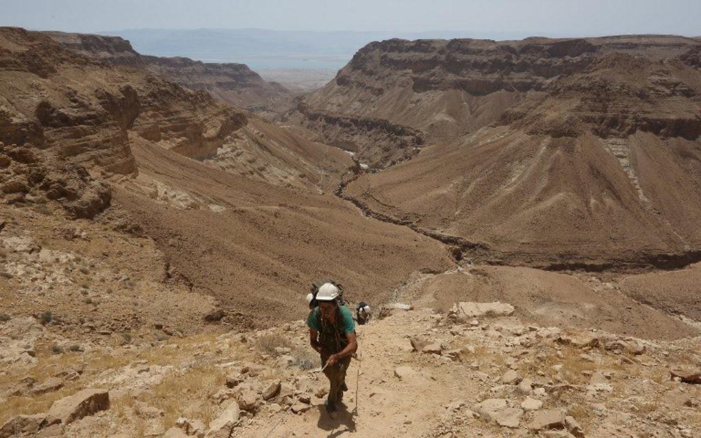 Dans le désert de Judée, un bénévole utilise une corde pour descendre dans une grotte du Canyon Tzeelim, au-dessus de la mer Morte (au fond), le 1er juin 2016. (Crédit : AFP PHOTO/MENAHEM KAHANA)