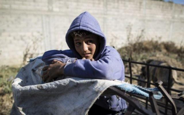 Karam al-Zaaneen, Palestinien de 13 ans, à larrière d'un chariot tiré par un âne après avoir collecté du plastqiue de recyclage dans une décharge de Beit Hanun, dans le nord de la bande de Gaza, le 18 mai 2016. (Crédit : AFP Photo/Mahmud Hams)