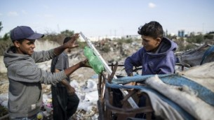 Karam al-Zaaneen (à droite), Palestinien de 13 ans, et son frère Mustafa, 18 ans, ont collecté du plastique de recyclage dans une décharge de Beit Hanun, dans le nord de la bande de Gaza, le 18 mai 2016. (Crédit : AFP Photo/Mahmud Hams)