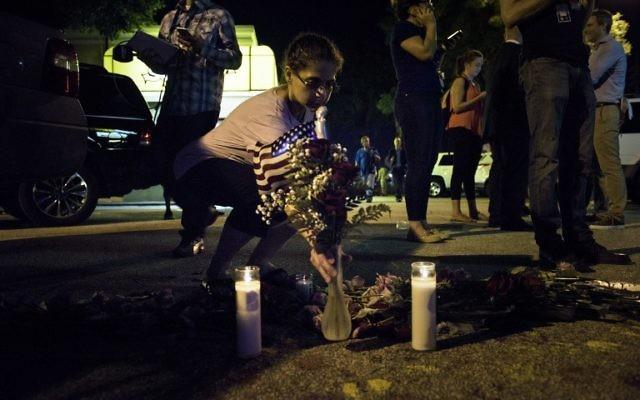 Sonia Drudge ajoute une fleur à un petit mémorial improvisé près de la boîte de nuit Pulse d'Orlando, le 12 juin 2016. (Crédit : AFP PHOTO/Brendan Smialowski)