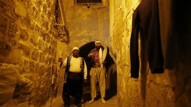Michel Ayoub (à droite), arabe israélien chrétien, assume la fonction de messaharati, chargé de réveiller les musulmans pendant le Ramadan pour le souhour, le repas qui précède l'aube, à Saint-Jean d'Acre, le 16 juin 2016. (Crédit : AFP/Ahmad Gharabli)