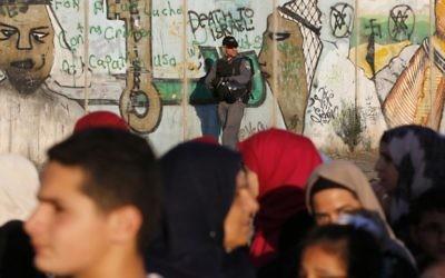 Un policier israélien surveille le checkpoint de Qualandia alors que des Palestiniens le franchissent , 17 juin 2016 (Crédit : AFP /ABBAS MOMANI)
