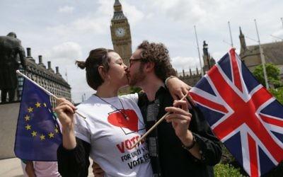 """La campagne du """"Remain"""", pour que le Royaume-Uni reste dans l'Union européenne, avait organisé une chaîne de baisers entre des personnes portant des drapeaux du Royaume-Uni et de l'Union européenne, devant la Chambre du parlement, à Londres, le 19 juin 2016. (Crédit : AFP/Daniel Leal-Olivas)"""