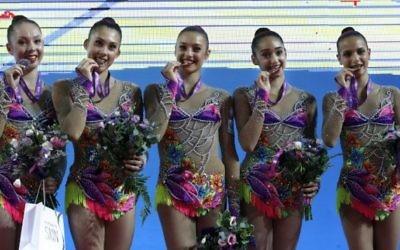 L'équipe de gymnastique rythmique israélienne célèbre sa médaille d'or sur le podium pendant les 32e championnats européens de gymnastique rythmique, qui se sont déroulés en Israël, à Holon, le 19 juin 2016. (Crédit : AFP/Thomas Coex)