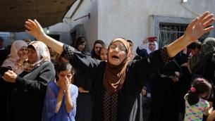 Les parents de l'adolescent palestinien Mahmoud Badran qui a été tué par les troupes israéliennes, le 21 Juin, pleurent lors de ses funérailles dans le village de Beit Ur-Tahta près de la ville de Ramallah en Cisjordanie le 23 juin 2016. (Crédit : AFP / ABBAS MOMANI)