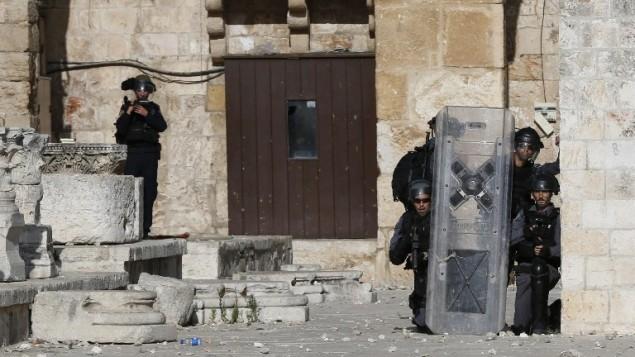 La police israélienne se met à couvert alors que des manifestants palestiniens jettent de pierres sur le mont du Temple à Jérusalem, au cours du troisième jour consécutif d'affrontements, le 28 juin 2016 (Crédit : AFP PHOTO/AHMAD GHARABLI)