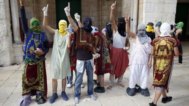 Des Palestiniens masqués pendant des affrontements avec la police sur le mont du Temple dans la Vieille Ville de Jérusalem, le 28 juin 2016 (Crédit : AFP/Ahmad Gharabli)