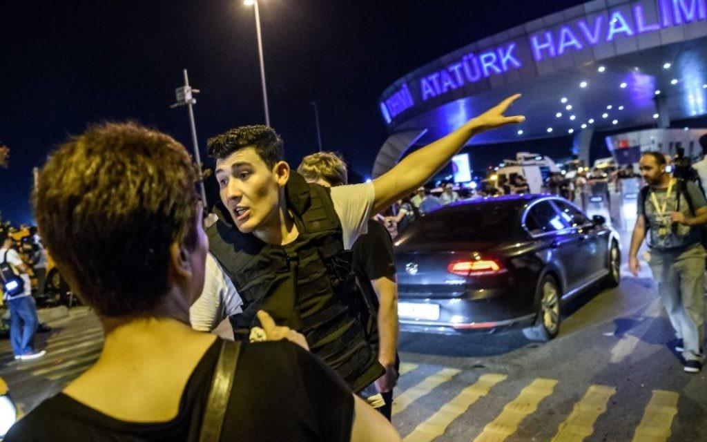 Un officier de police turc dirige les passagers de l'aéroport Atatürk à Istanbul, le 28 juin 2016, après une attaque terroriste dans le plus grand aéroport de Turquie (Crédit : AFP PHOTO / OZAN KOSE)