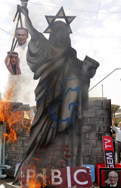 Une maquette de la Statue de la Liberté ornée d'une étoile de David sur la tête et de portraits de l'ancien Premier ministre britannique Tony Blair et du ministre saoudien des Affaires étrangères Adel al-Jubeir est incendiée pendant une manifestation de la Journée al-Quds [Jérusalem] à Téhéran, en Iran, le 1er juillet 2016. (Crédit : AFP/Atta Kenare)