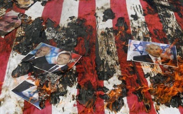 Portrait du roi de Bahreïn Hamad (en haut à gauche), du Premier ministre israélien Benjamin Netanyahu et du président turc Recep Tayyip Erdogan sur un drapeau américain en flammes pendant une manifestation de la Journée al-Quds [Jérusalem] à Téhéran, le 1er juillet 2016. (Crédit : Atta Kenare/AFP)